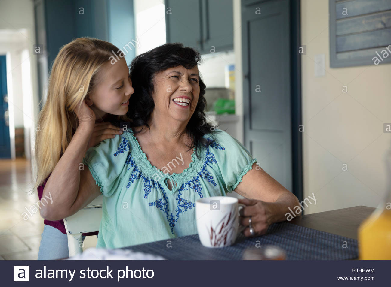 Petite-fille et grand-mère affectueuse Latinx à table de cuisine Photo Stock