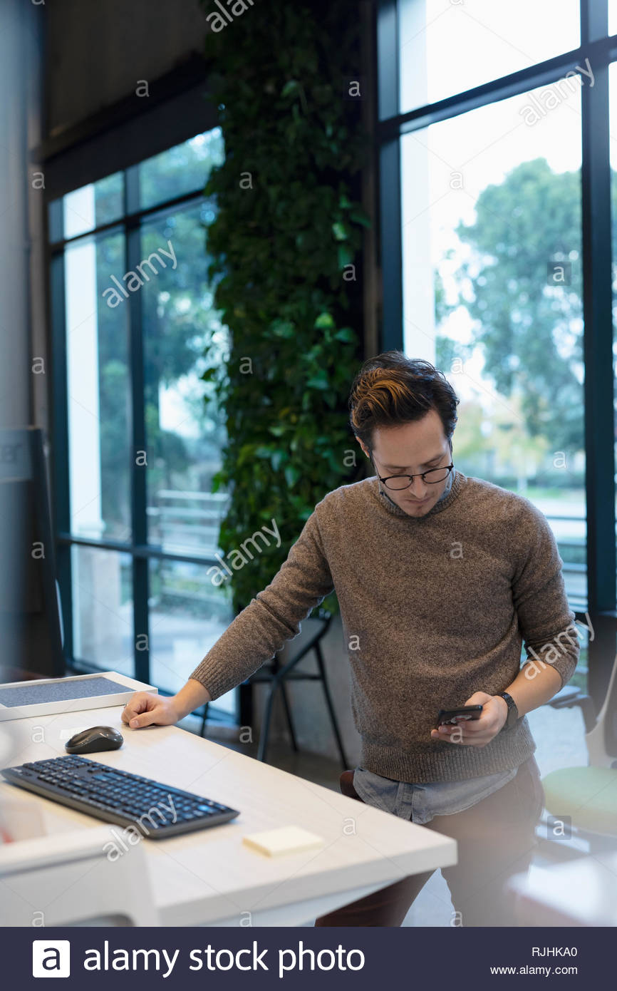 Businessman using smart phone at sit-stand desk in office Photo Stock