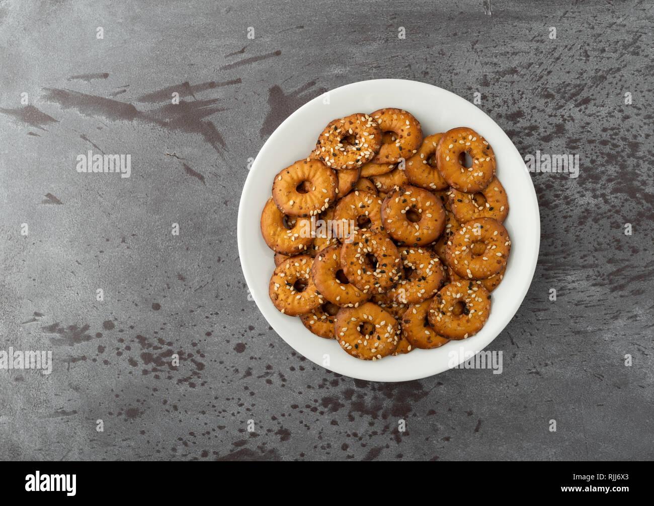 Vue de dessus d'une plaque blanche remplie de petits copeaux de bagel avec un assortiment de graines sur un fond gris, éclairé par la lumière naturelle. Banque D'Images