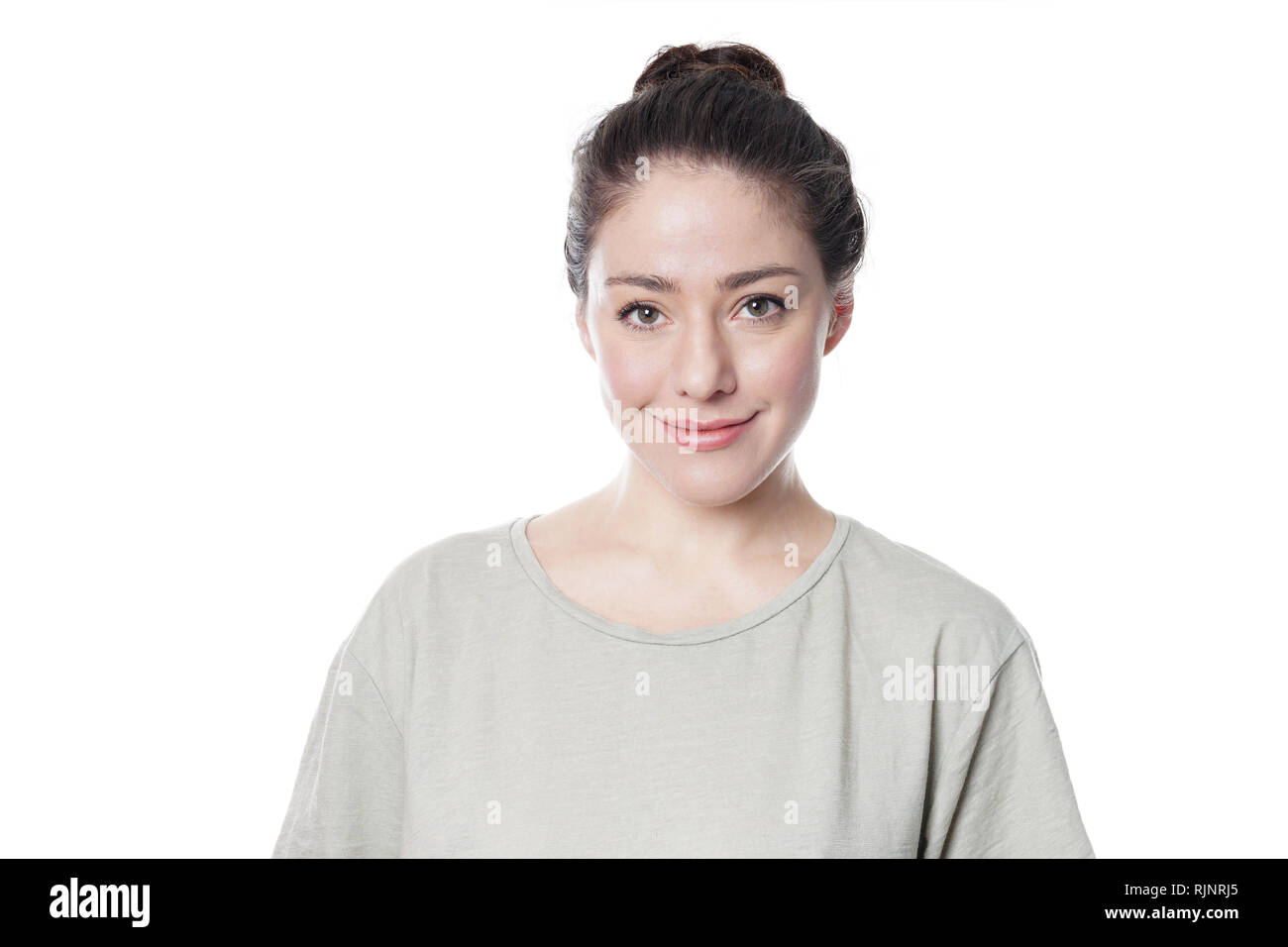 Jeune femme smilng dans son 20s avec le maquillage naturel et brunette hair bun isolé sur fond blanc Photo Stock