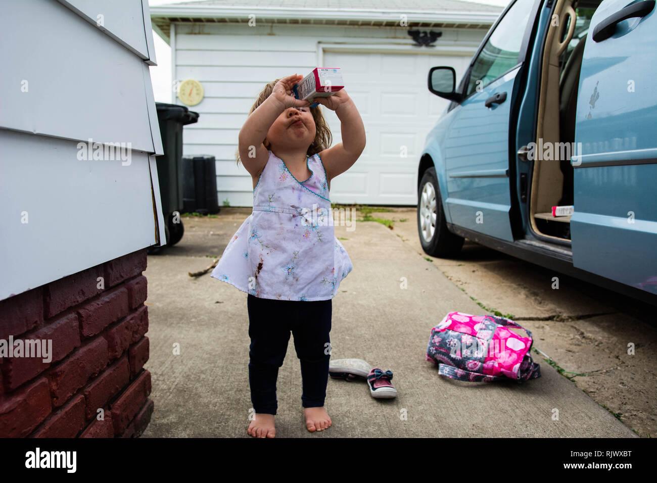 A 2 ans, prend un verre de jus d'une boîte sur une journée chaude à l'extérieur d'un van avec la porte ouverte. Photo Stock