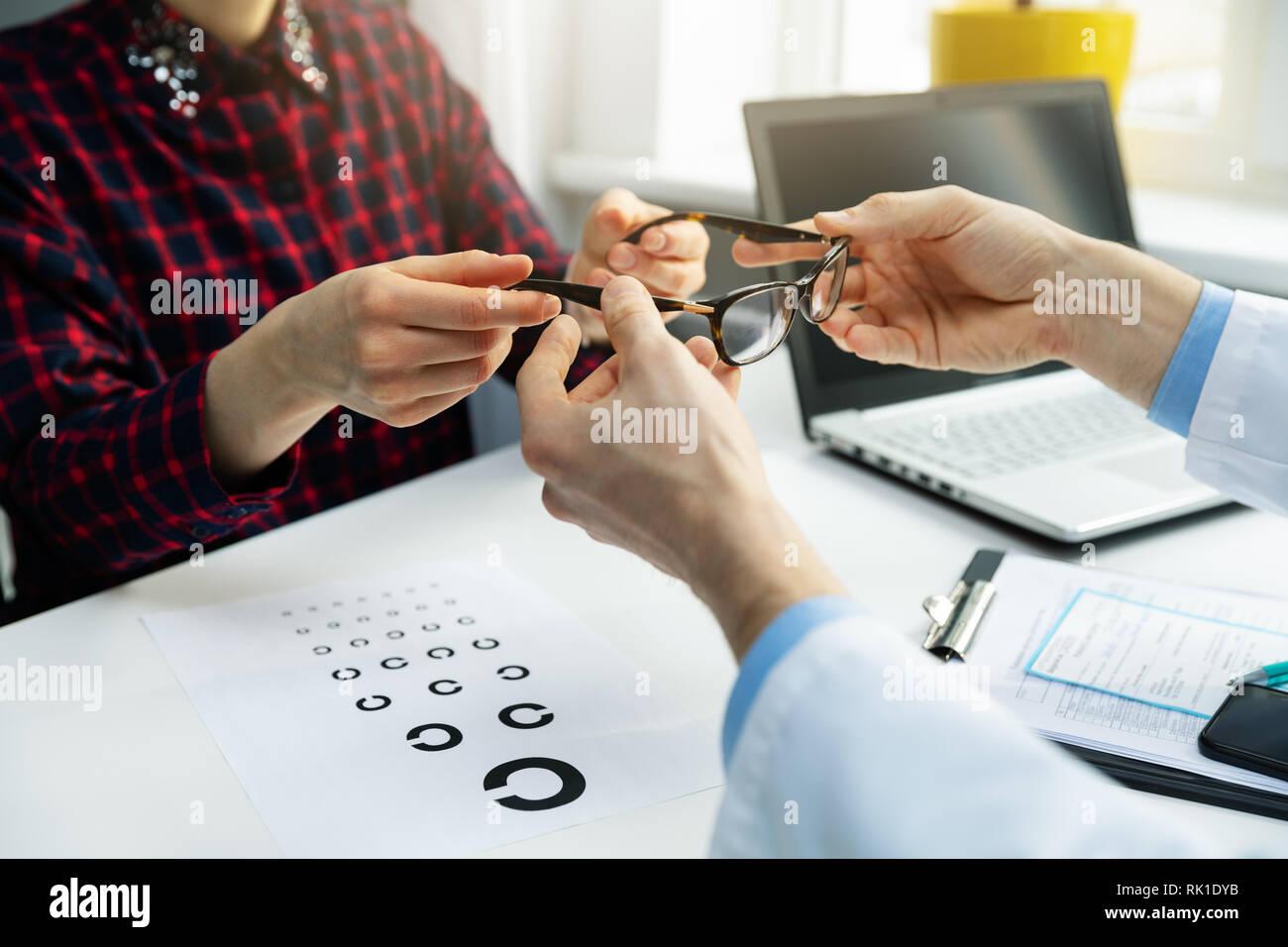 Optométriste visiter - femme obtenir son nouveau bureau de l'opticien à lunettes Banque D'Images