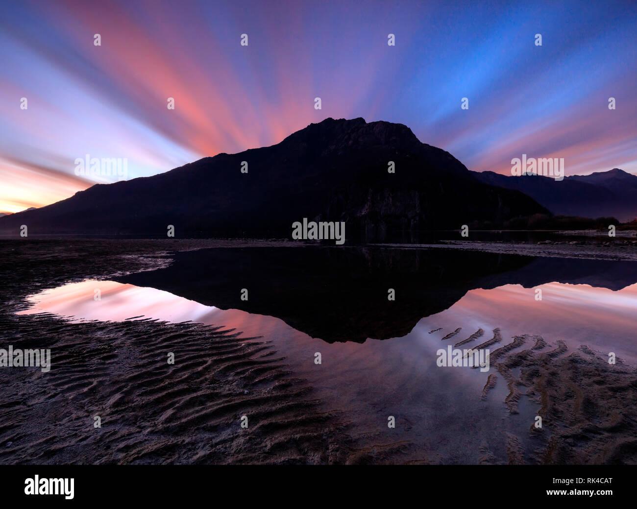 Coucher Soleil nuages en miroir dans l'eau, Novate Mezzola, Chiavenna, vallée de la Valteline, province Sondrio, Lombardie, Italie Banque D'Images