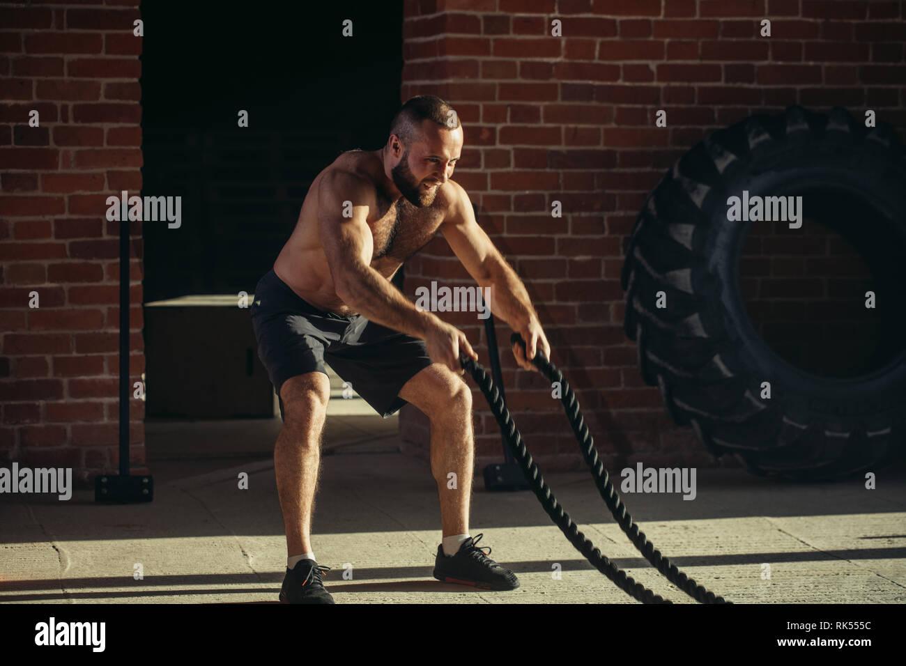 Jeune homme athlétique avec corde bataille faire de l'exercice dans la salle de sport fitness formation fonctionnelle. Rope contribuent à engager tous les groupes musculaires en même temps, alors que l'ens Banque D'Images