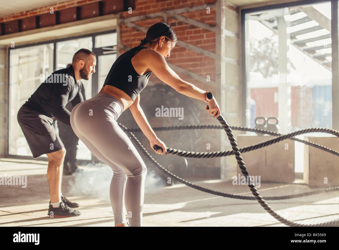 Caucasian couple fit l'exercice avec des cordes à la bataille de sport. Femme et homme habillé en tenue de sport formation ensemble faisant combattre corde d'entraînement, avec p Banque D'Images
