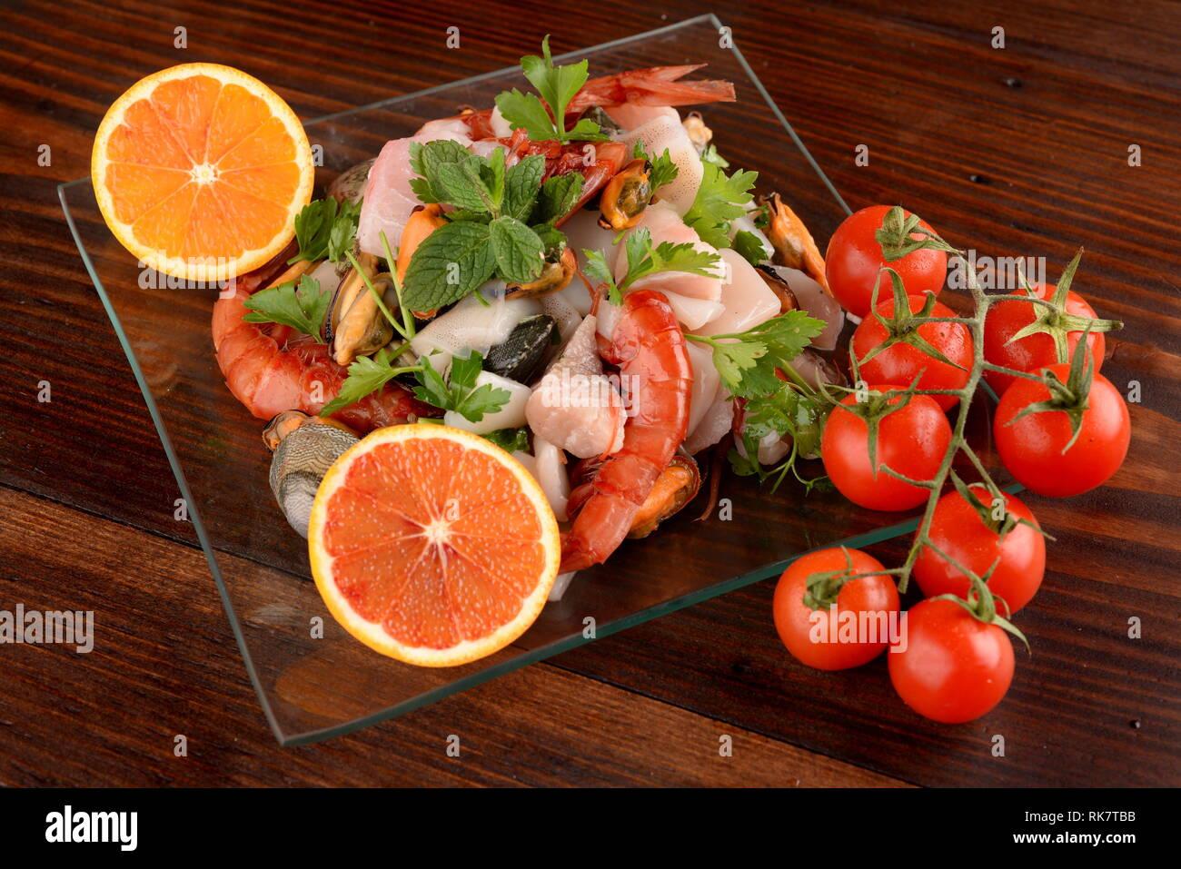 Plats en verre avec le poisson bonito mollusques et coquillages matières sur la planche de bois Banque D'Images