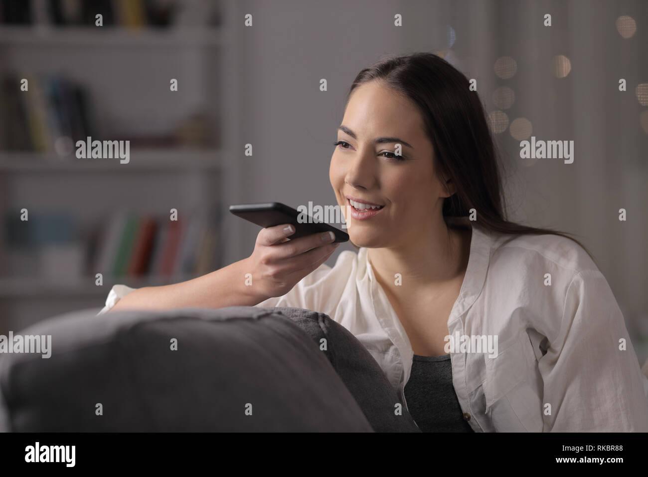 La femme de la nuit en utilisant la reconnaissance vocale téléphone assis sur un canapé dans la nuit à la maison Banque D'Images