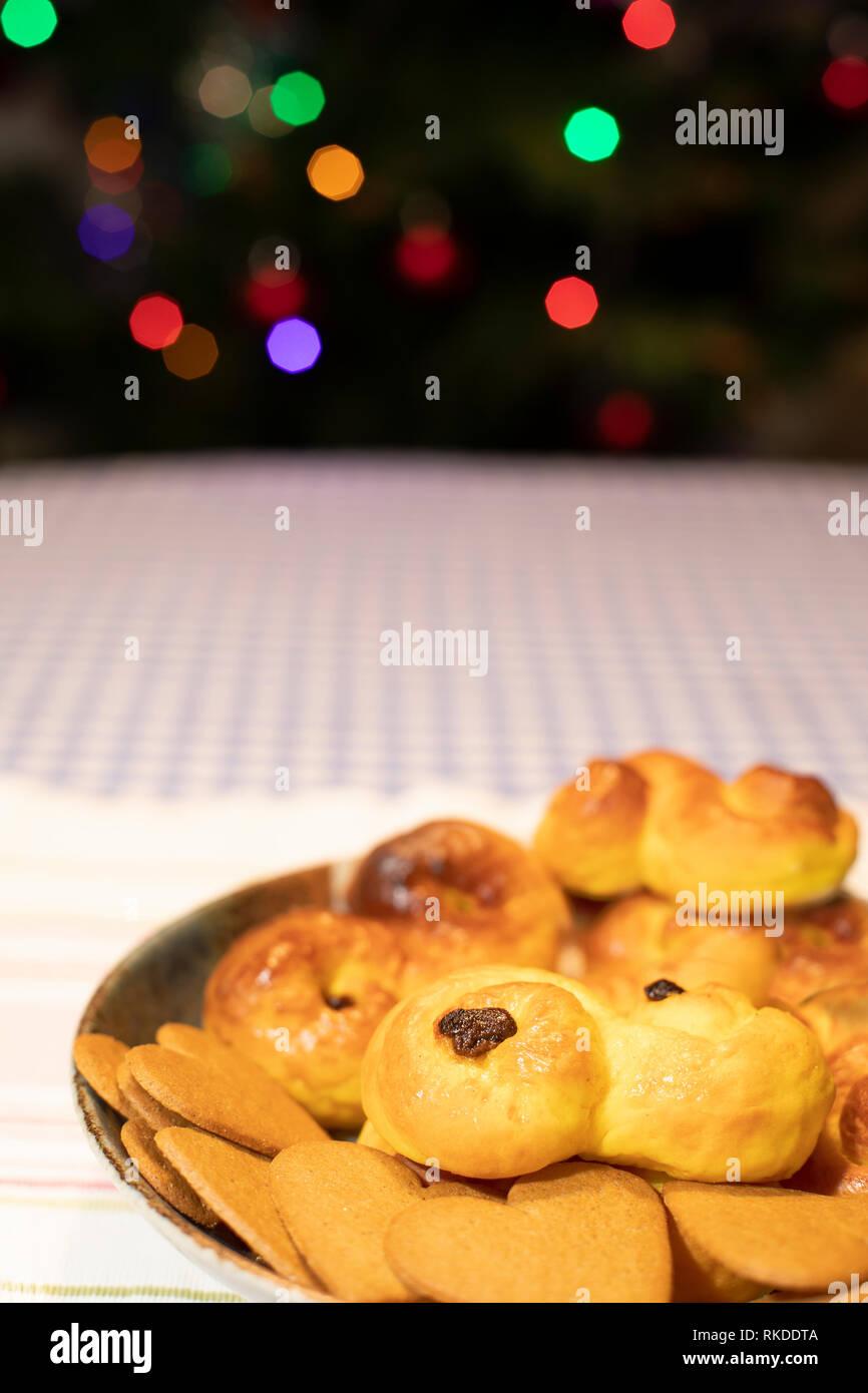 Un plat traditionnel suédois de pain au safran et Ginger Snaps avec couleur floue des lumières d'arbre de Noël en arrière-plan. Banque D'Images