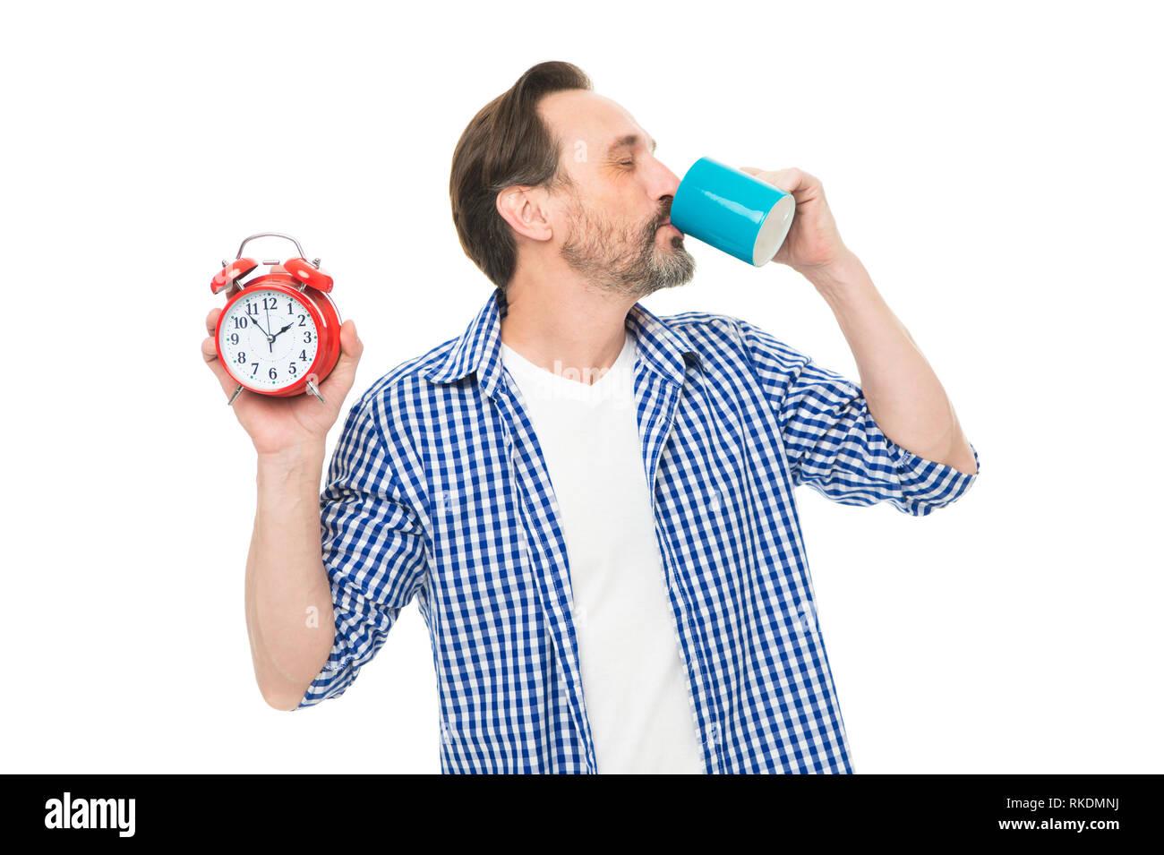 Et que vous soyez excité. Homme mature barbus boire du café avec l'horloge dans la main. Homme mature avec réveil de boire une boisson chaude. Son temps de boire le café du matin. À partir journée dans la bonne humeur. Photo Stock
