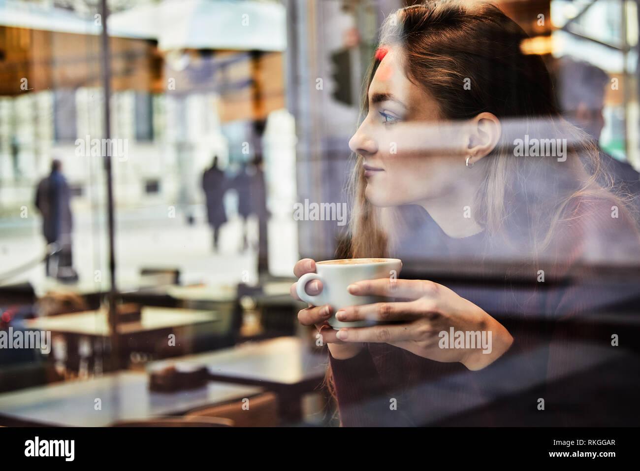 Girl daydreaming tandis que détient une tasse de café au café du coin, concept photo au travers de la fenêtre de l'effet de la ville avec la réflexion Banque D'Images