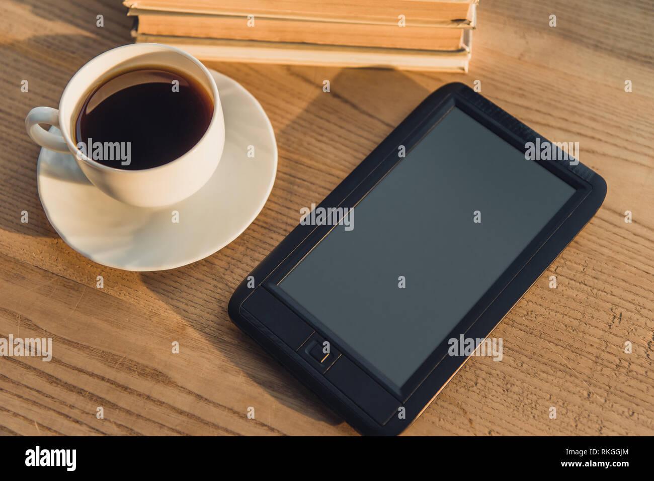 E-reader noir avec écran blanc situées près de tasse à café sur le tableau Photo Stock