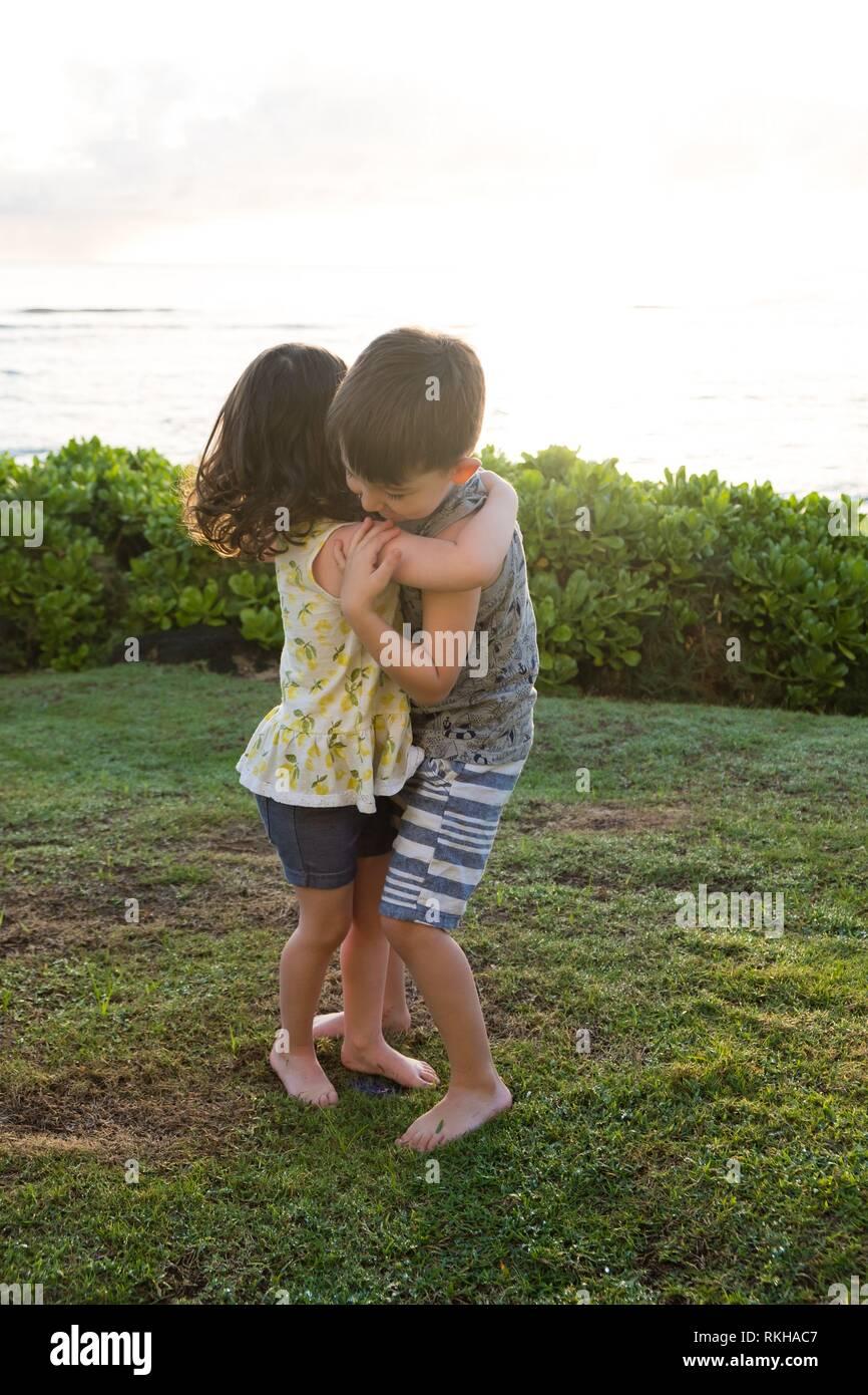 Frères et sœurs hugging at the beach dans Oahu Hawaii avec une belle lumière naturelle au lever du soleil. Banque D'Images