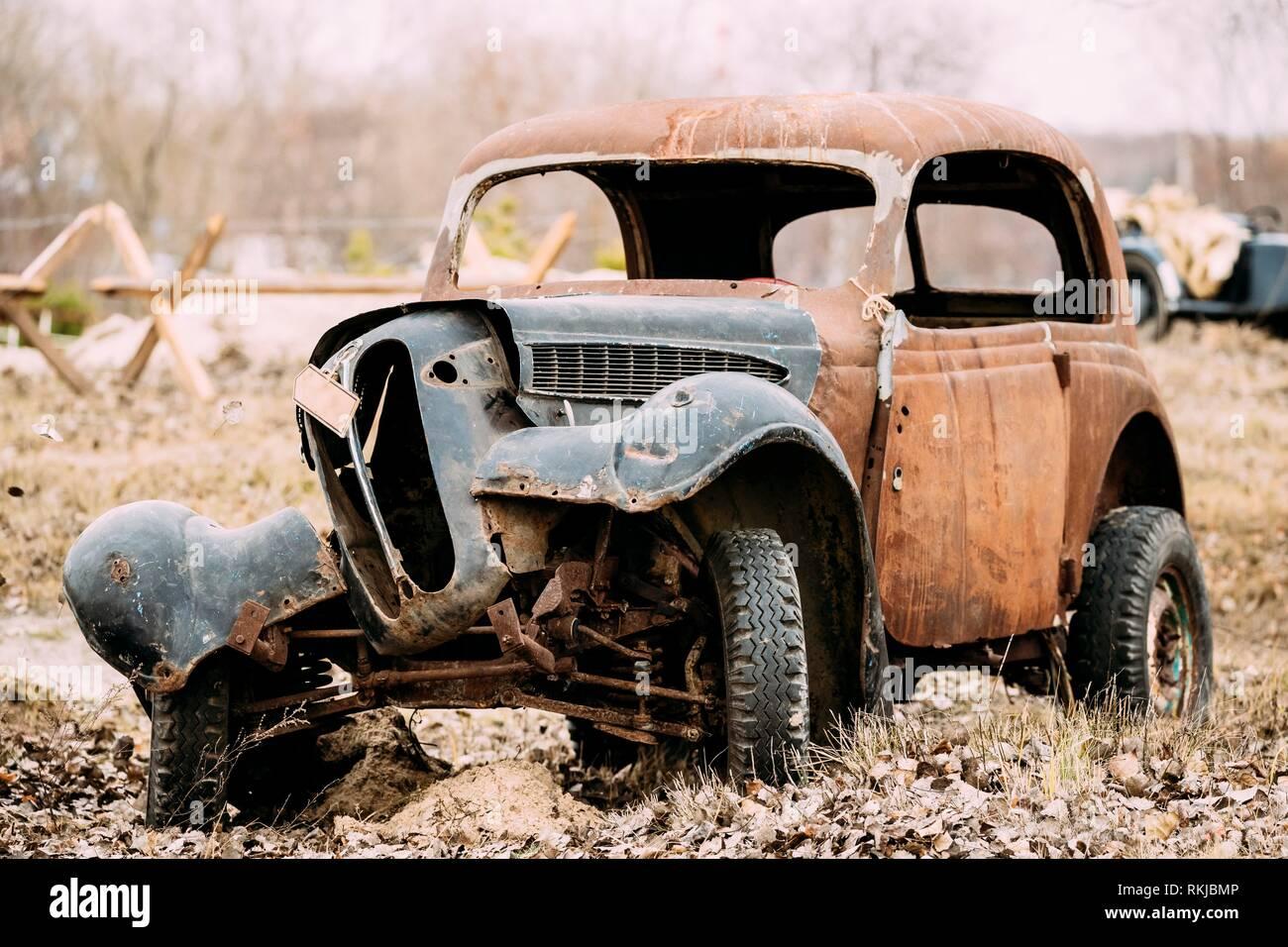Vieille voiture rouillée s'est écrasé cassé abandonné pendant la Seconde Guerre mondiale est dans un champ d'automne. Banque D'Images