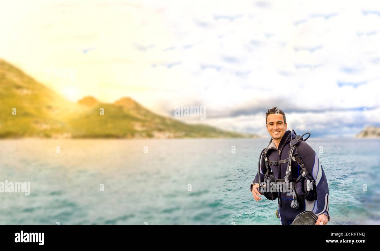 Young handsome man smiling plongeur isolé prêt à plonger dans l'eau froide combinaison, palmes, ceinture de plomb et de oxigen à Karaburun, Izmir. La Turquie Photo Stock