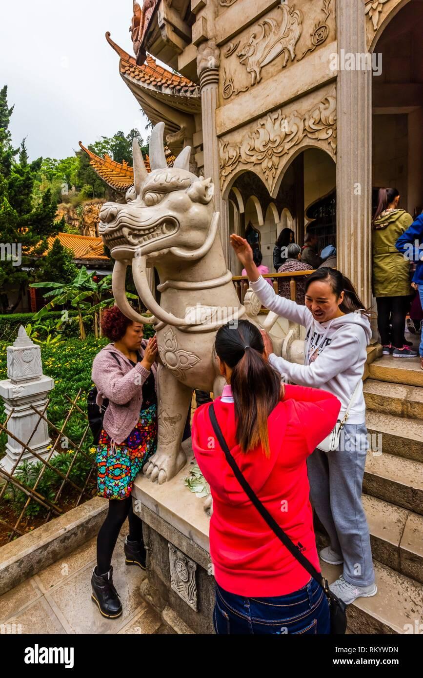 Les Bouddhistes de toucher une statue de gardien pour la bonne chance au Temple du sud de bouddhisme, Temple Yuantong, Kunming, Province du Yunnan, Chine. Photo Stock