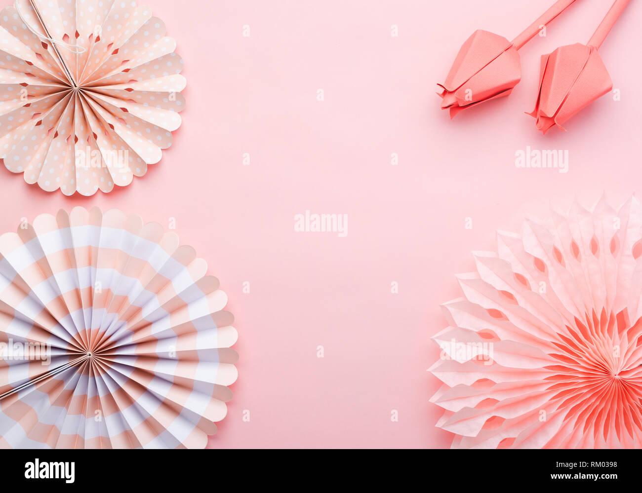 Le papier chinois fans de couleurs pastel rose sur table, vue de dessus, l'espace de copie de texte, de la mise au point sélective. Fleurs en papier en corail vivant. Photo Stock
