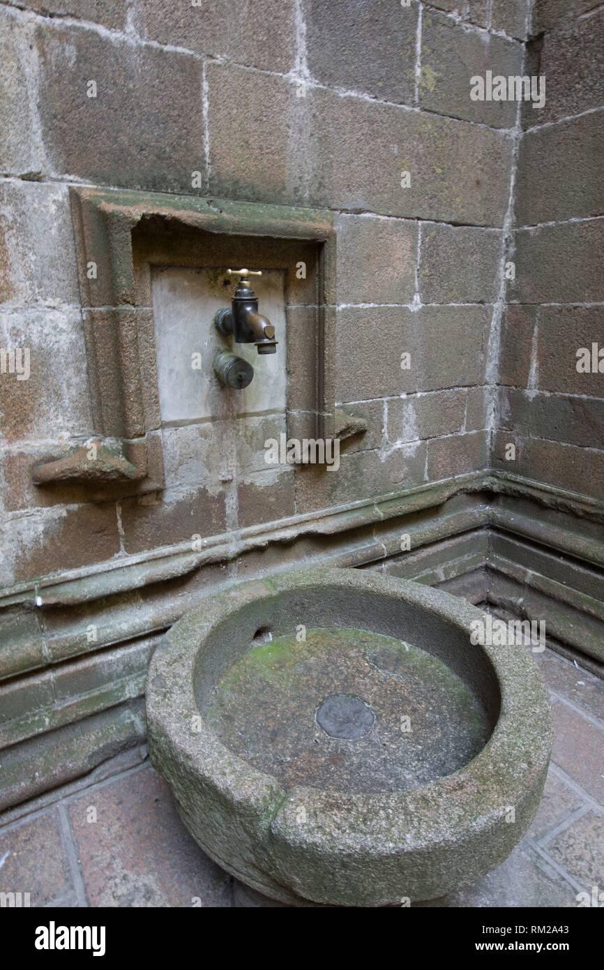 Fontaine en pierre et de grandes robinet robinet laiton à l'intérieur du Mont Saint Michel. Normandie, France Banque D'Images
