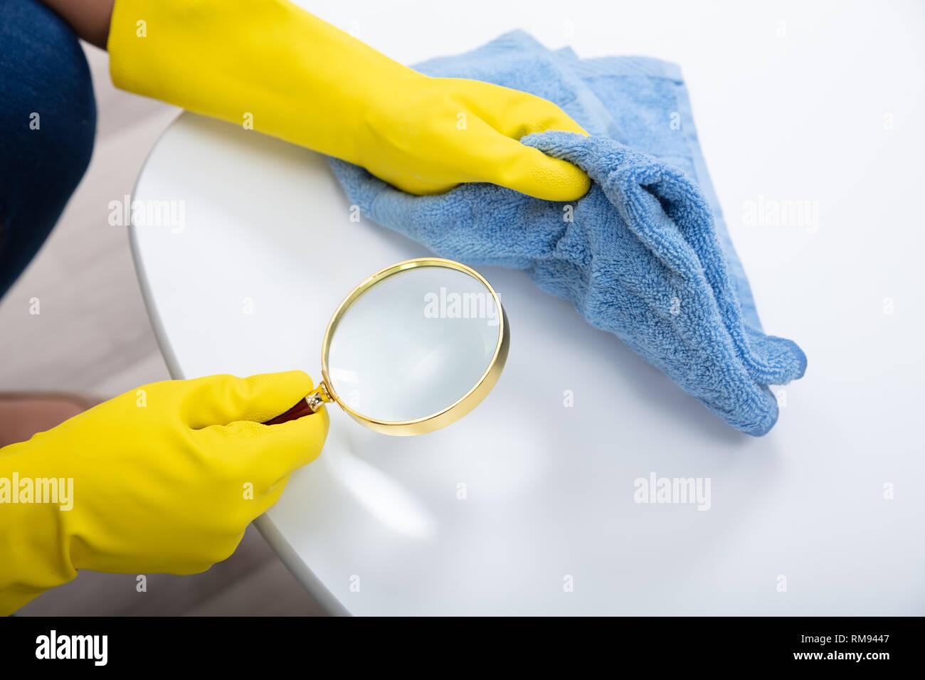 Concierge part portant des gants jaunes examiner Tableau à l'aide de loupe et nappes Photo Stock