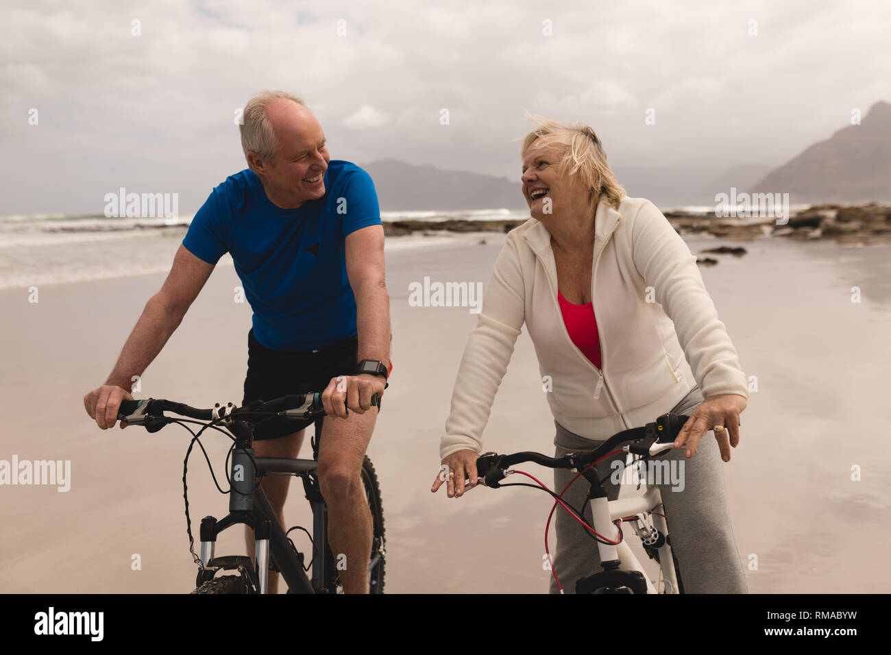 Senior couple riding a bicycle de bonne humeur sur la plage Photo Stock