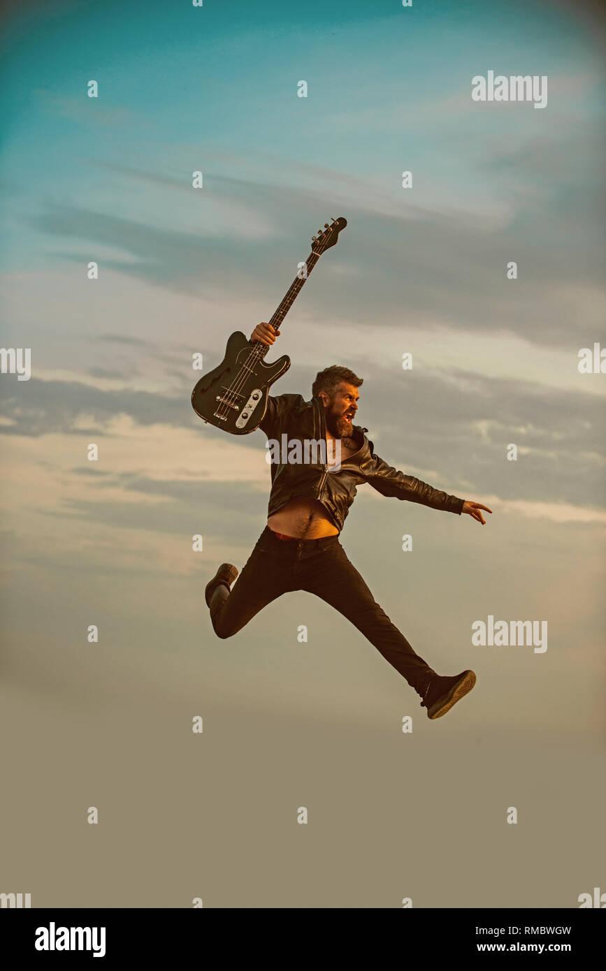 La liberté dans ses veines. La liberté, l'homme barbu jump avec guitare on blue sky Photo Stock
