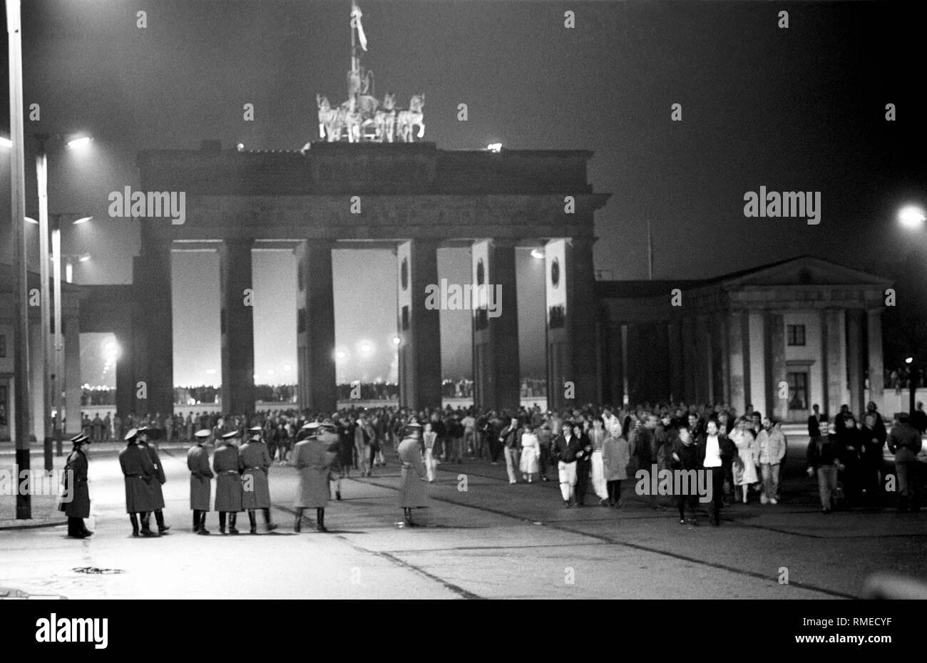 """Vue depuis l'Est de Berlin à la porte de Brandebourg dans la nuit du 9 au 10 novembre, après la """"chute du Mur"""". Les citoyens de l'Est et l'ouest de Berlin se tenir sous la porte et sur le mur (derrière), des troupes frontalières de la RDA sont à l'avant et sous la porte. Photo Stock"""