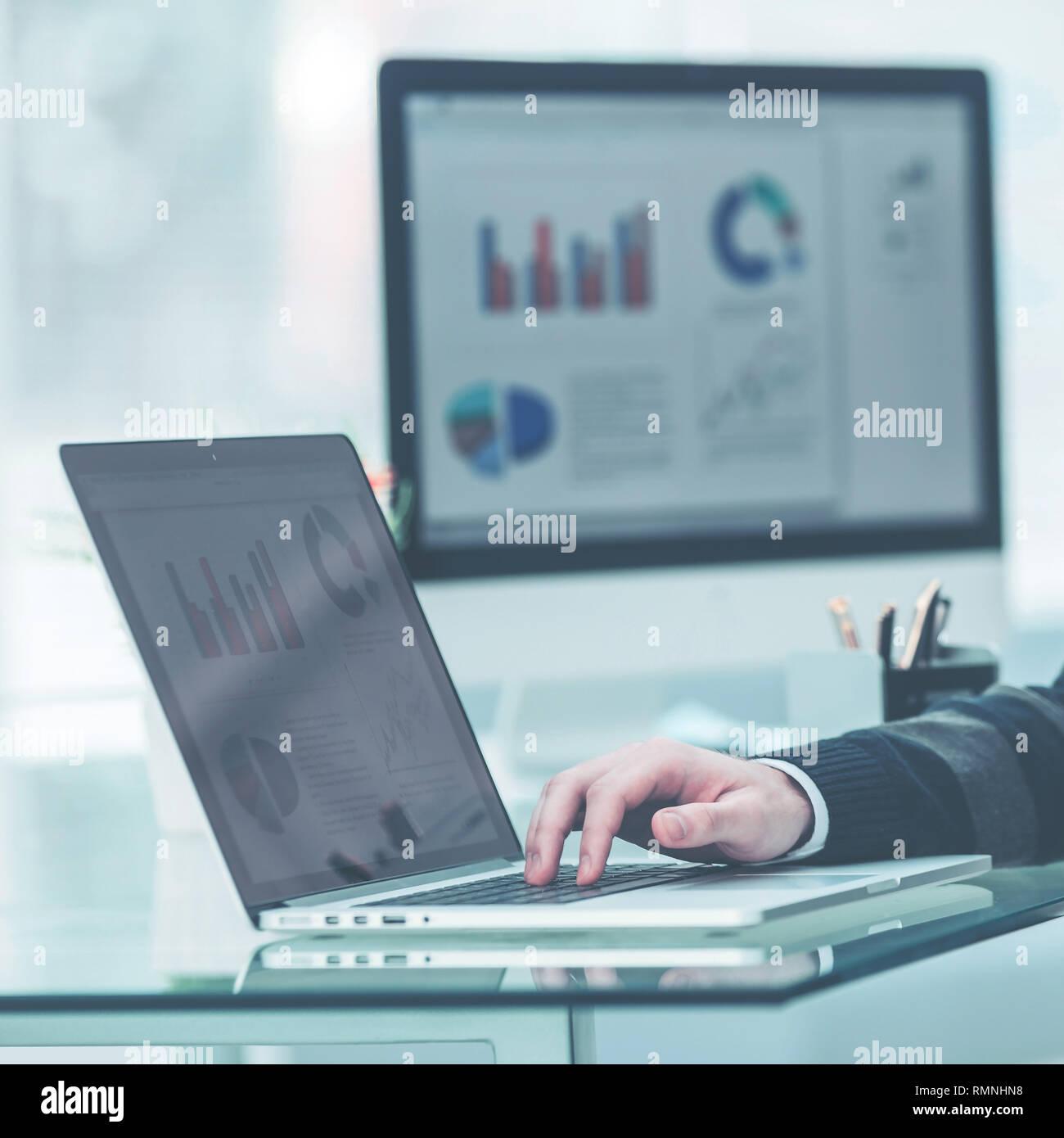 Spécialiste des finances travaille sur un ordinateur portable avec les cartes et plans de commercialisation financière Photo Stock