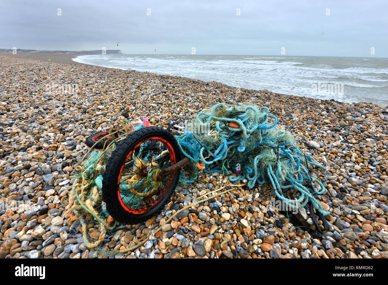 Vieux vélo emmêlé dans un filet de pêche en plastique, abandonné sur une plage, East Sussex, UK Photo Stock