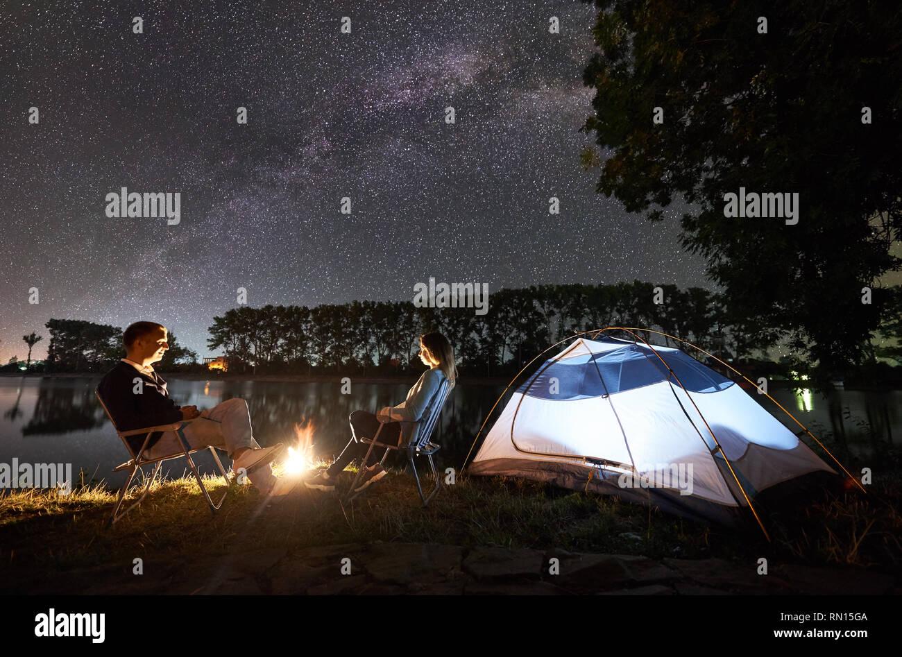 Nuit camping à bord du lac. L'homme et la femme amis assis sur des chaises près de camp et allumé tente, avec des avis de soir ciel plein d'étoiles et Milky Way, les lumières de la ville, sur l'arrière-plan. Banque D'Images