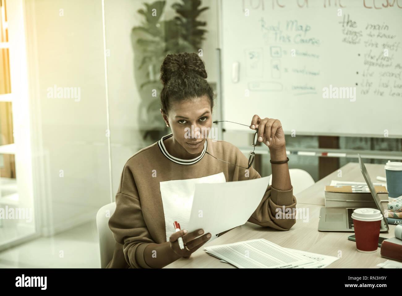 Enseignant avec cheveux bun se sentir fatigué pendant le contrôle des tests finaux Photo Stock