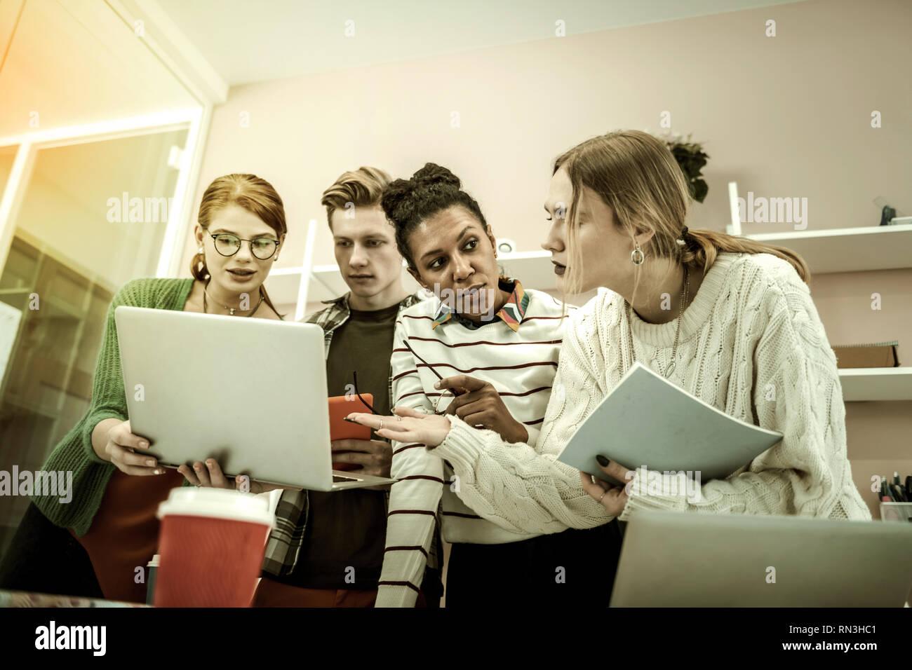 Quatre étudiants profitant de leur étude de groupe le week-end. Photo Stock