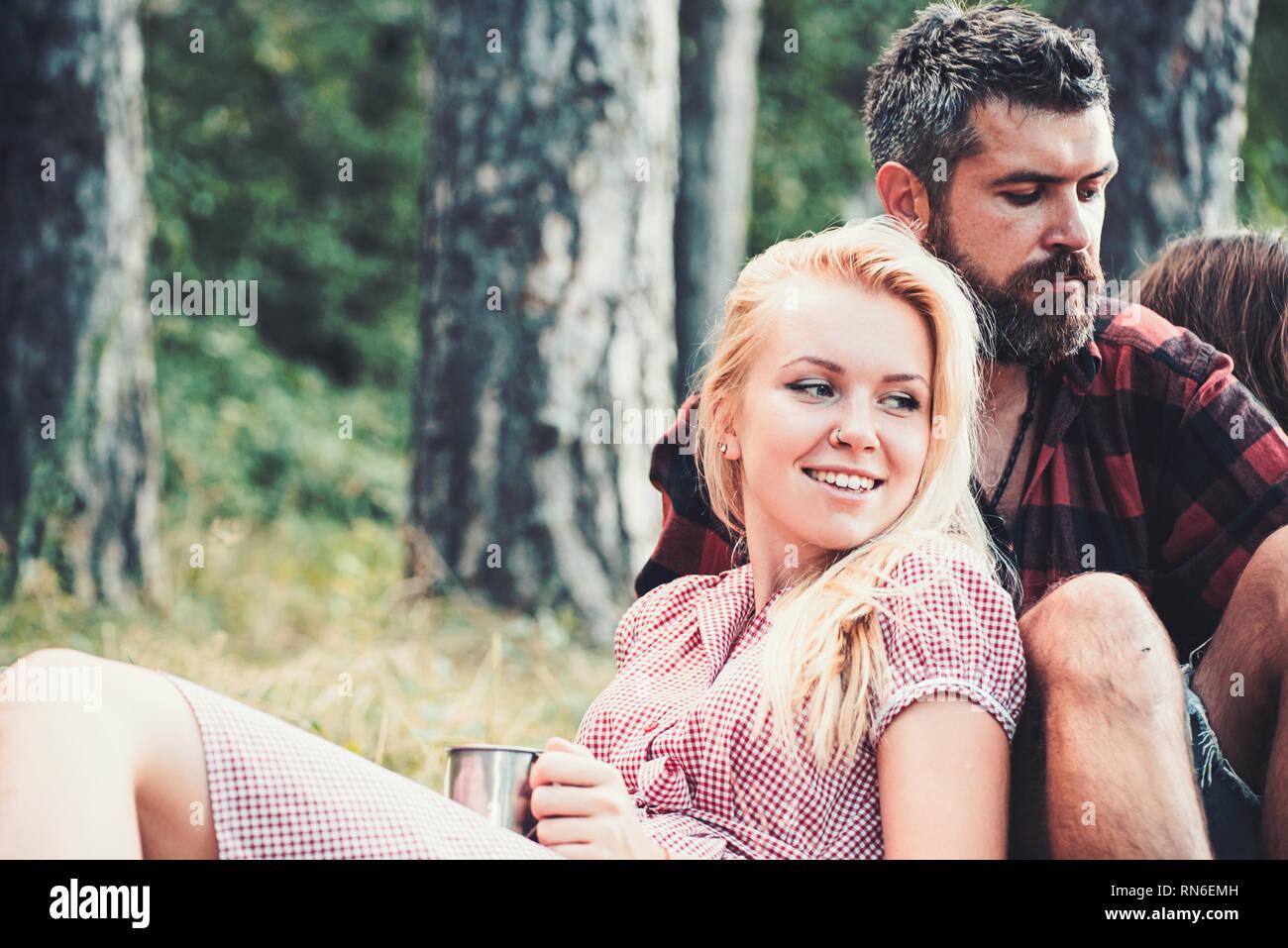 Fille blonde appuyée sur son petit ami. Groupe d'amis assis sur l'herbe à côté du feu de camp. Week-end romantique dans la nature Banque D'Images
