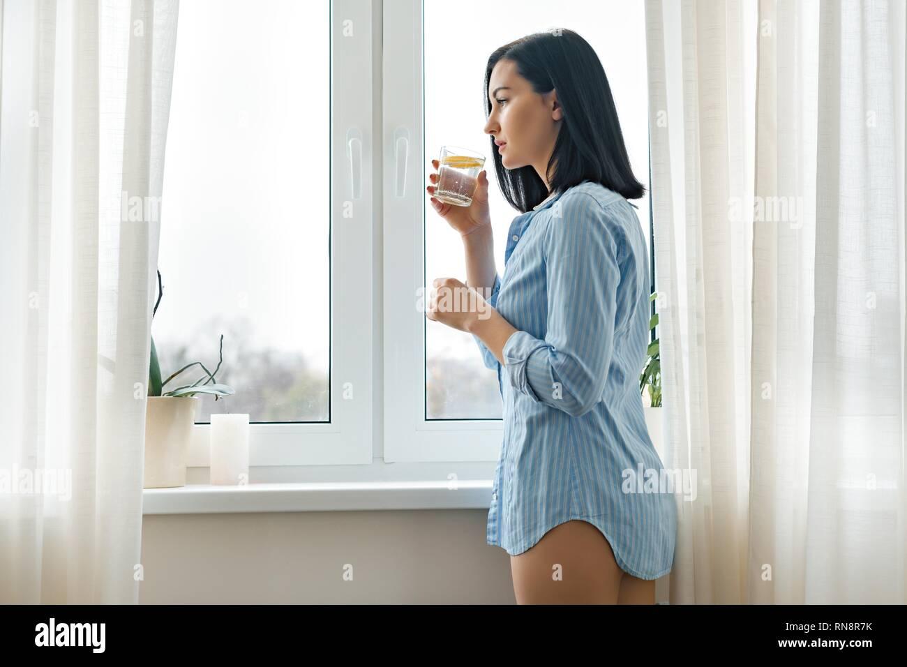 Mode de vie sain, l'alimentation, l'antioxydant. Matin verre d'eau avec du citron dans les mains de jeune femme Photo Stock