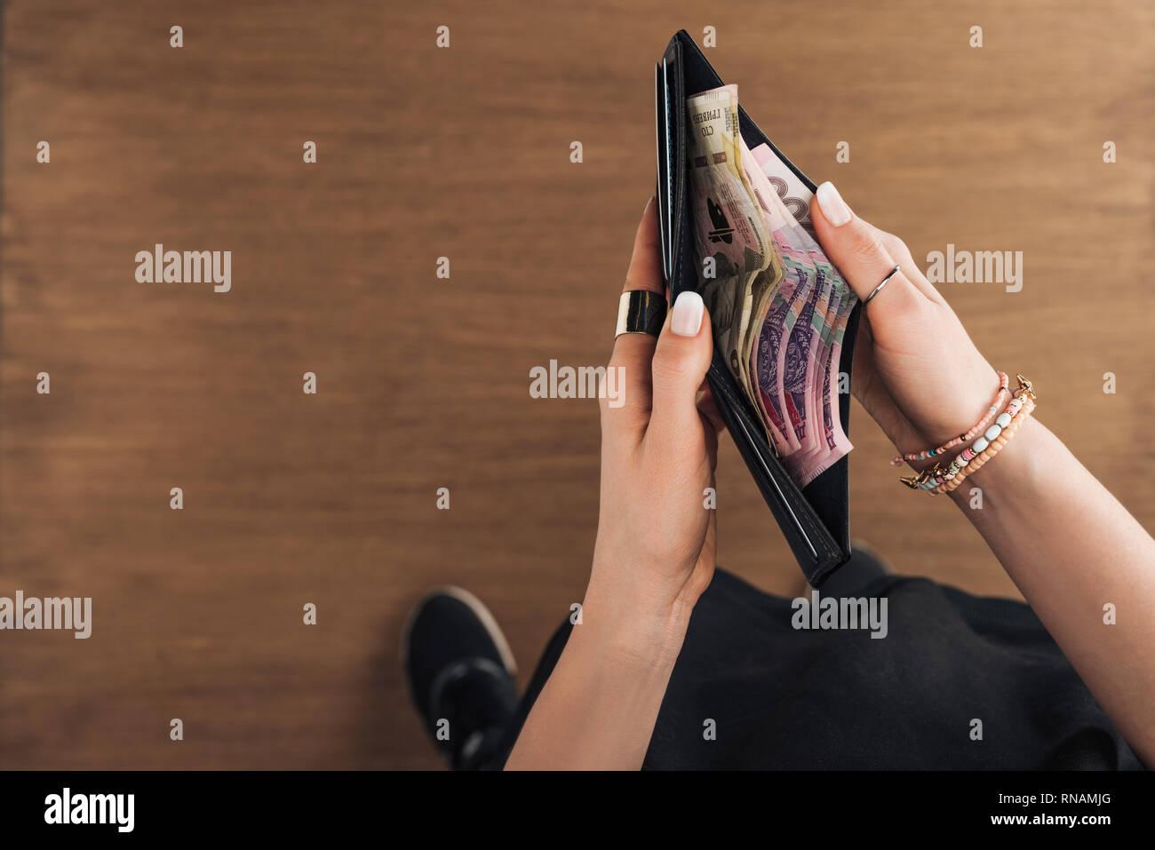 Vue de dessus de woman holding wallet avec billets hryvnia sur fond de bois Banque D'Images