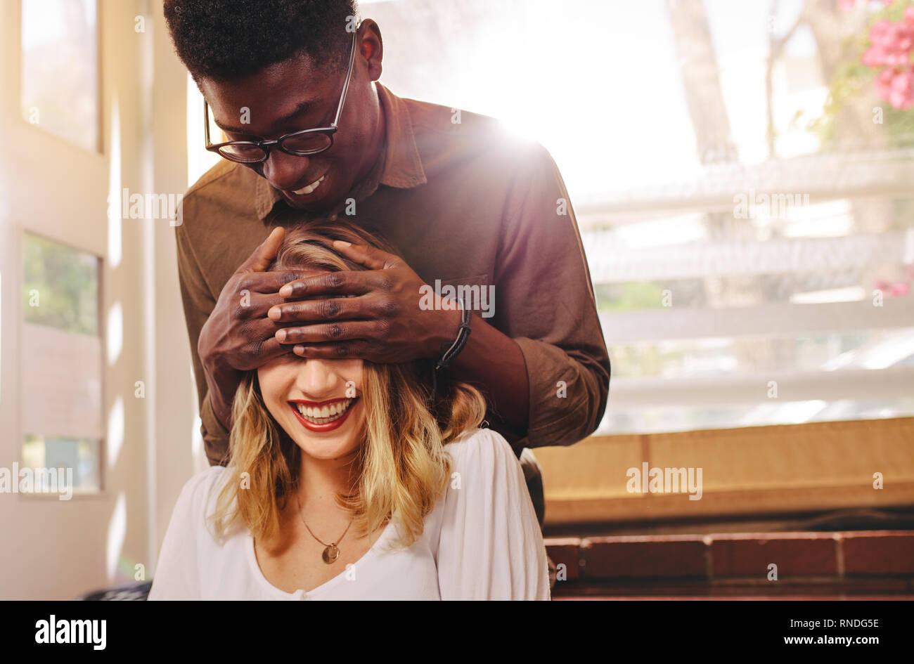 Jeune homme debout derrière son amie et couvrant ses yeux dans le café. Couple sur la date, l'homme femme surprenant du coffee shop. Banque D'Images
