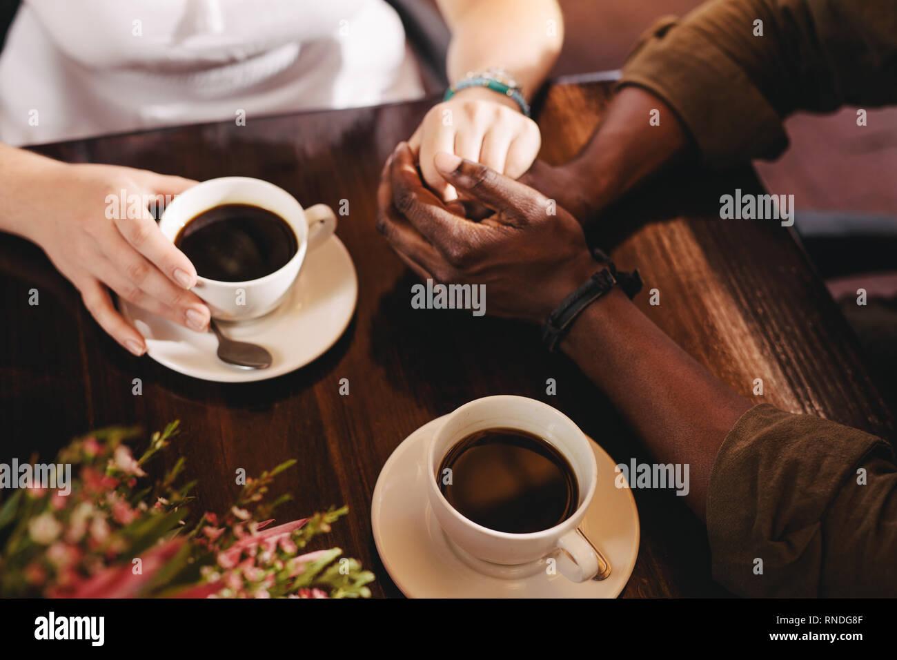 Couple sur une date assis à une table de café. Close up of man holding mains d'une femme sur une table avec des tasses de café par le côté. Banque D'Images