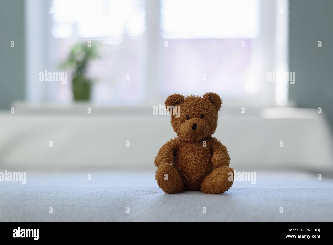 Petit ourson en peluche sur le lit blanc. Concept de la petite enfance Photo Stock