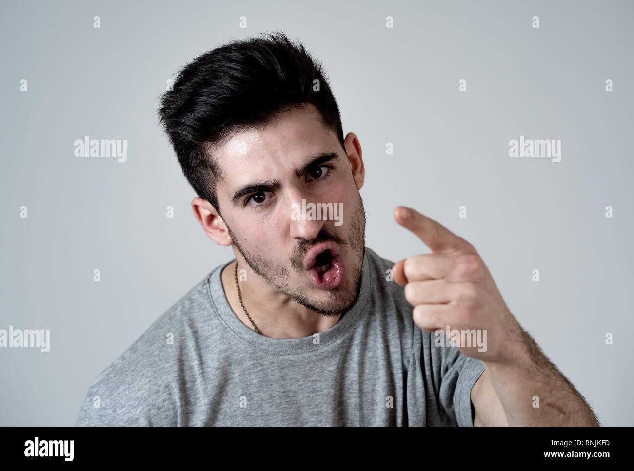 Close up portrait of young man with violence à visage en colère et fou furieux montrant adapte et doigt à la caméra. Les droits de l'expressi faciale Photo Stock