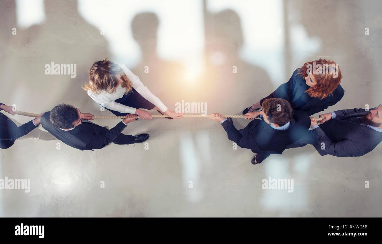 Homme et femme d'affaires rivales en compétition pour la commande en tirant la corde double exposition. Photo Stock