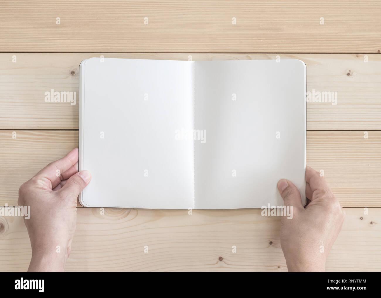Vide poche ouverte livre maquette, catalogue des revues, ou note modèle avec texture papier copyspace dans les mains sur la table en bois de pin blanc Photo Stock