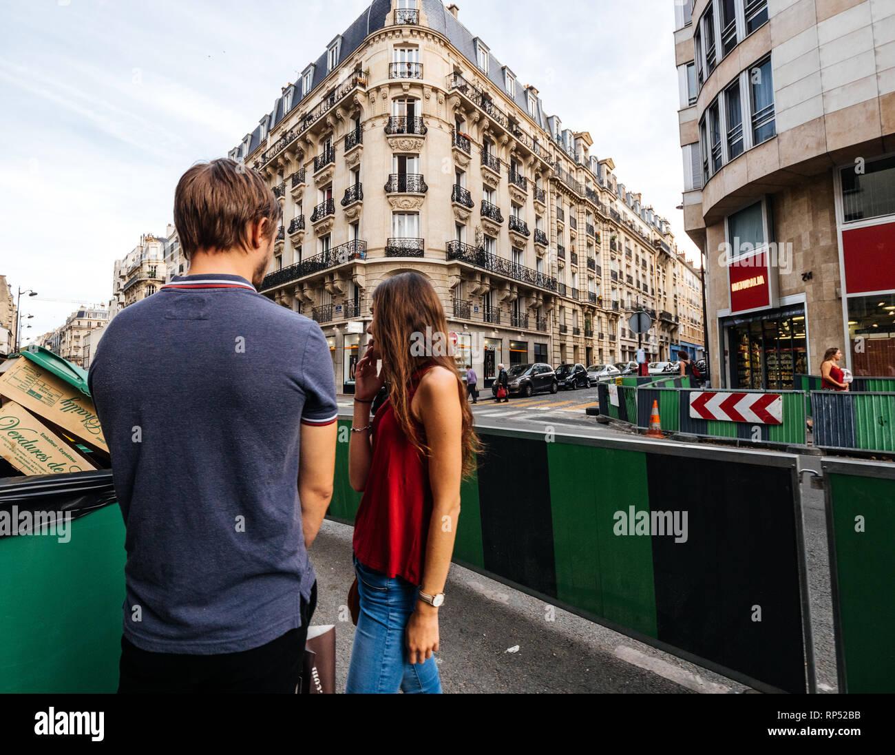 PARIS, FRANCE - OCT 13, 2018: elegant couple français à parler au coin de la rue avec bâtiment haussmannien dans l'arrière-plan Banque D'Images