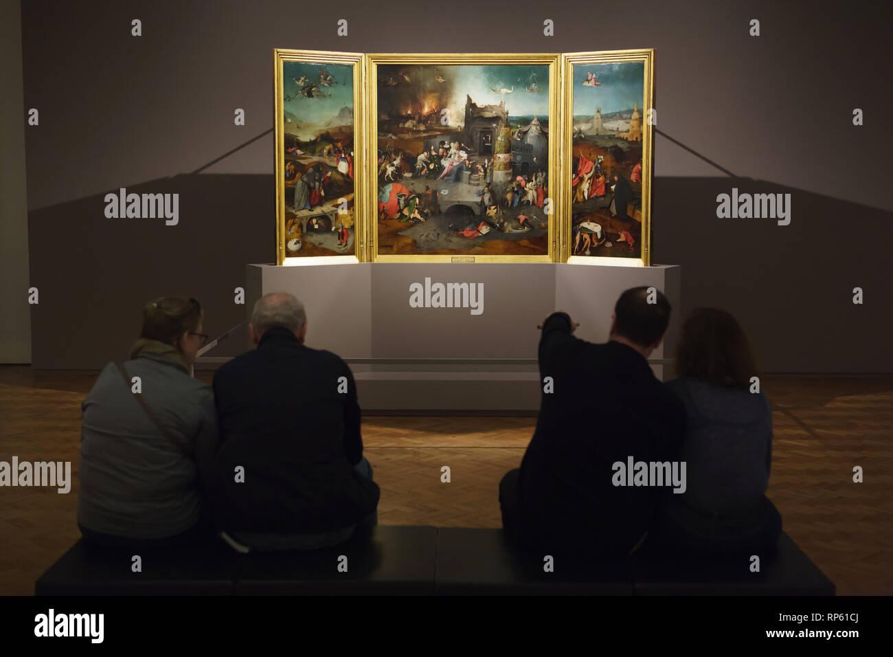 """Visiteurs en face de l'autel le triptyque """"La Tentation de Saint Antoine"""" par Dutch peintre Jérôme Bosch (1490-1500) affiché dans le Musée National d'Art Ancien (Museu Nacional de Arte Antiga) à Lisbonne, Portugal. Photo Stock"""