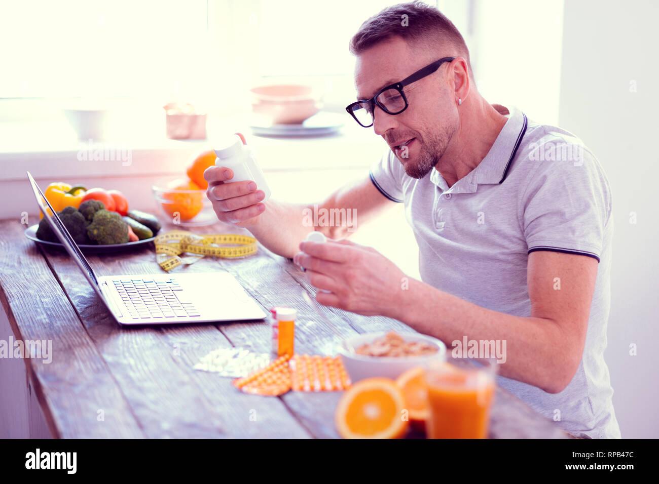 L'homme conduisant un régime équilibré tenant son matin de vitamines Photo Stock