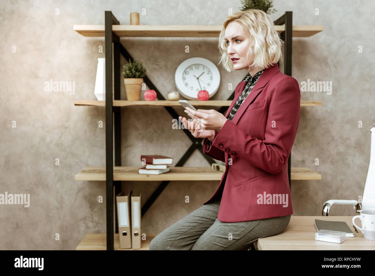 Bon sérieux lady in red jacket obsolètes s'appuyant sur la surface de la table Photo Stock