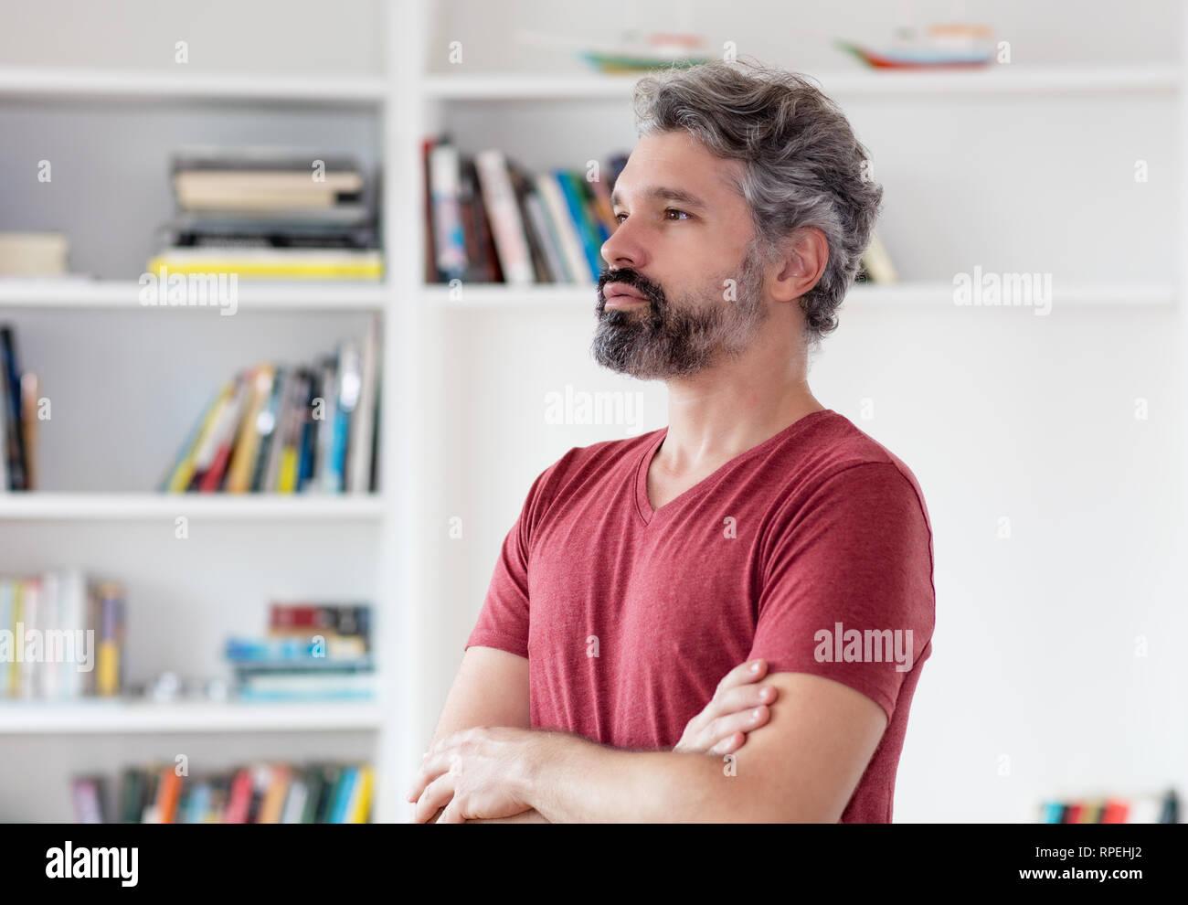 Penser l'homme d'âge moyen allemand avec les cheveux gris à l'intérieur à la maison Banque D'Images