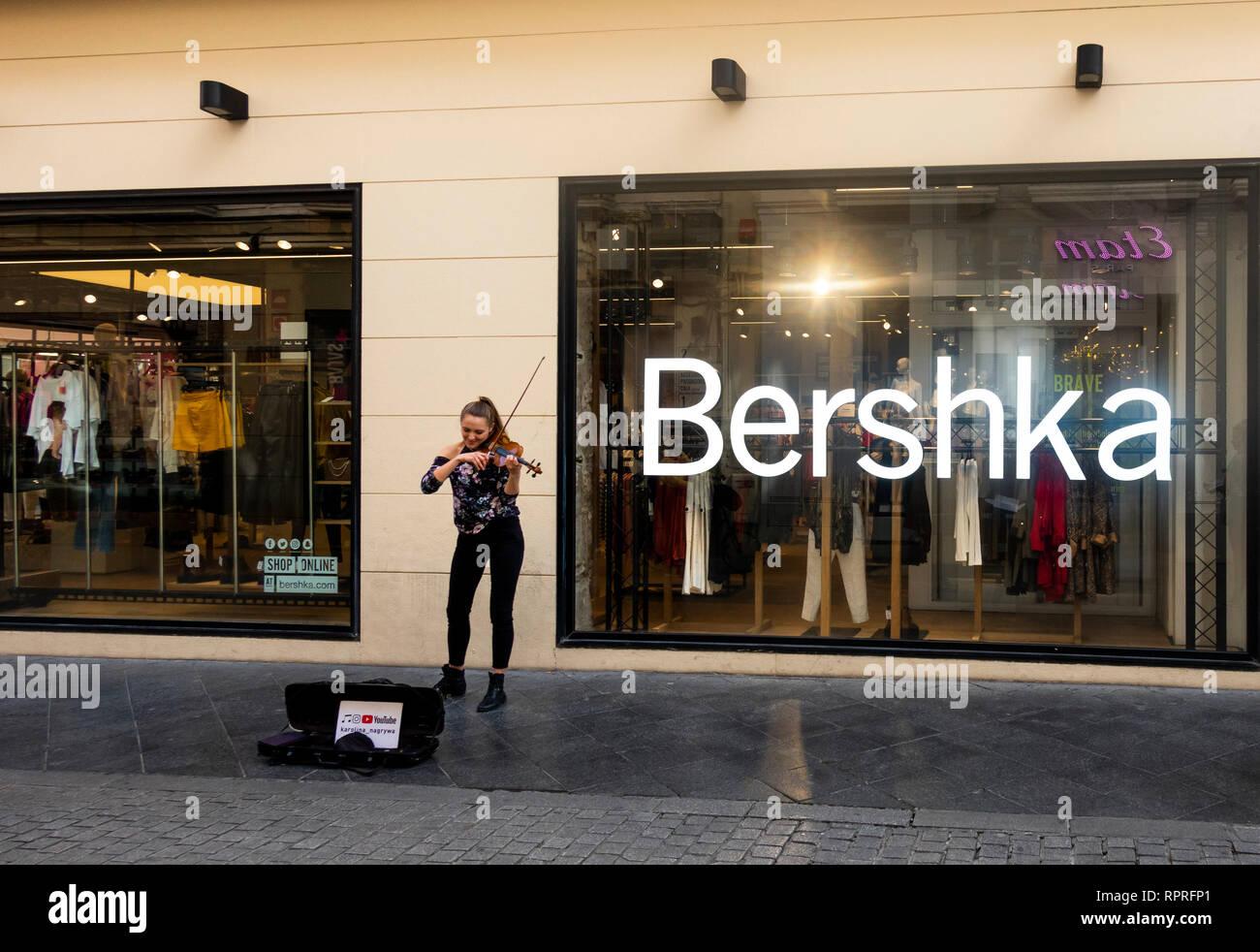 bef3dec1f7e80 Jeune femme jouant du violon musicien ambulant en face d un magasin de  vêtements à