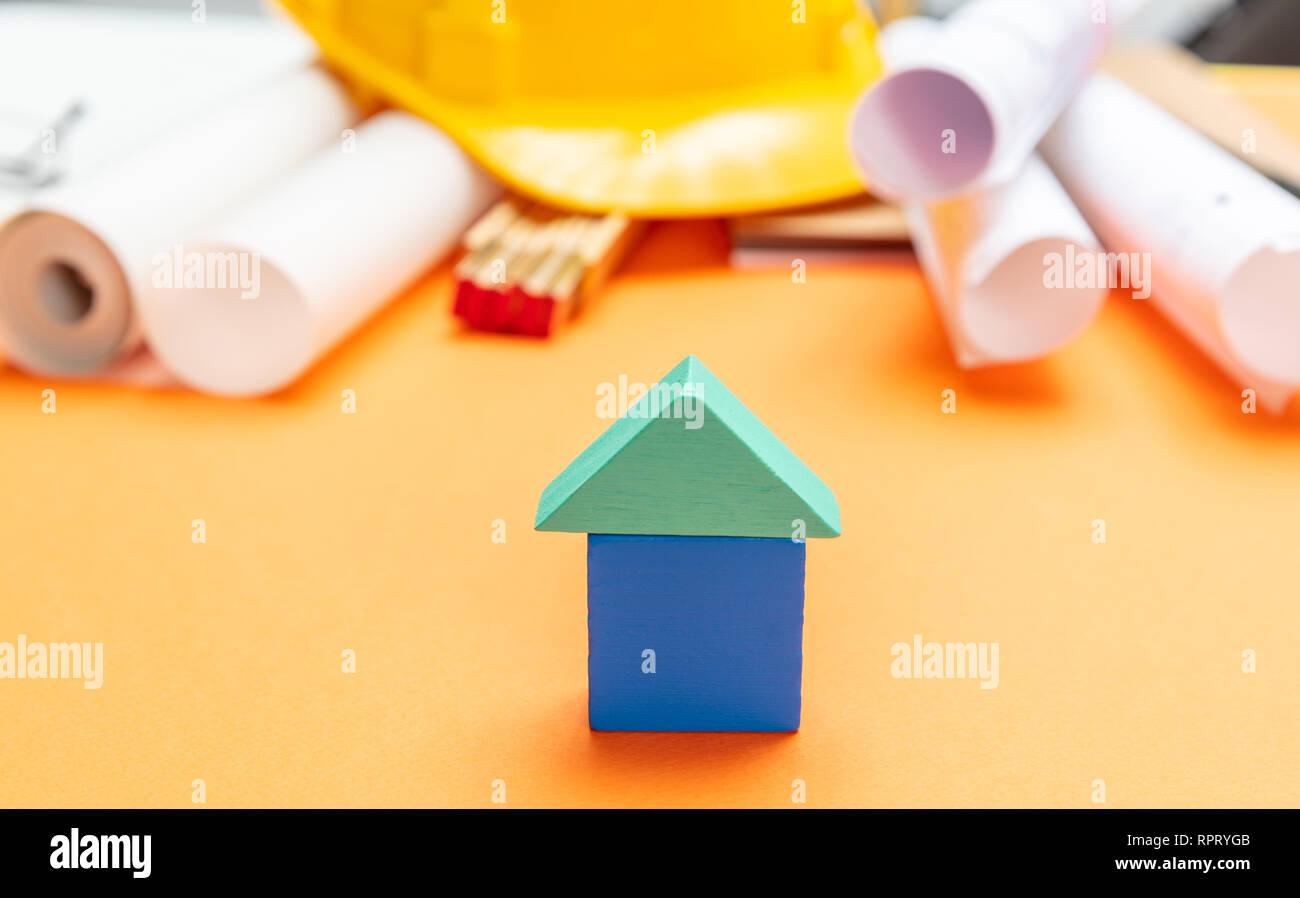 Concept immobilier. Petite maison modèle, casque et des plans de projet sur fond de couleur orange Banque D'Images