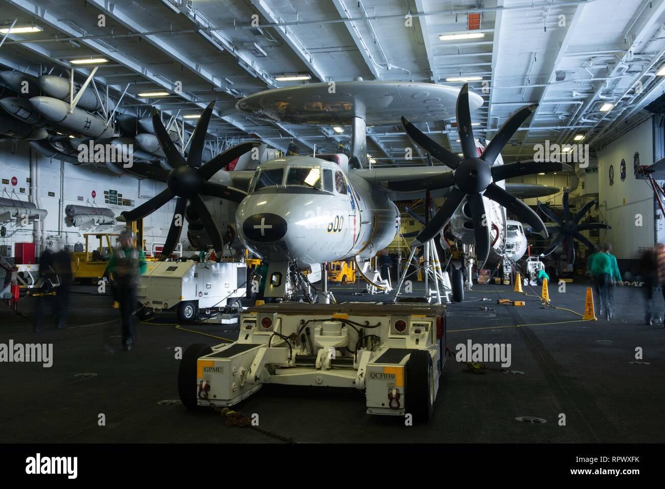 Les marins de la marine américaine en commun autour d'un E-2C Hawkeye, affecté à l'Escadron aéroporté de détection lointaine de l'opérateur (VFF) 117, dans la zone à bord du porte-avions USS JOHN C. STENNIS (CVN 74) dans l'océan Pacifique, le 19 février, 2019. Le John C. Stennis est déployé pour la 7è zone des opérations de la flotte à l'appui de la sécurité et de la stabilité dans la région Indo-Pacifique. (U.S. Photo par marine Spécialiste de la communication de masse Seaman Apprentice Jordanie Ripley) Photo Stock