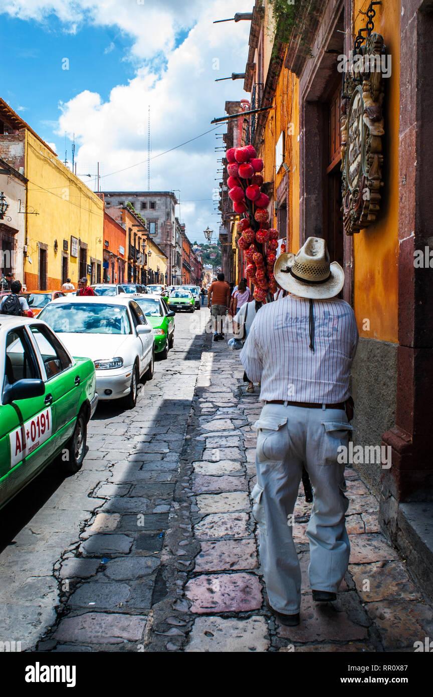 Le Mexique, San Miguel de Allende rue animée scène avec candy apple vendeur marche sur la rue pavée. Ville pittoresque est une destination populaire. Photo Stock