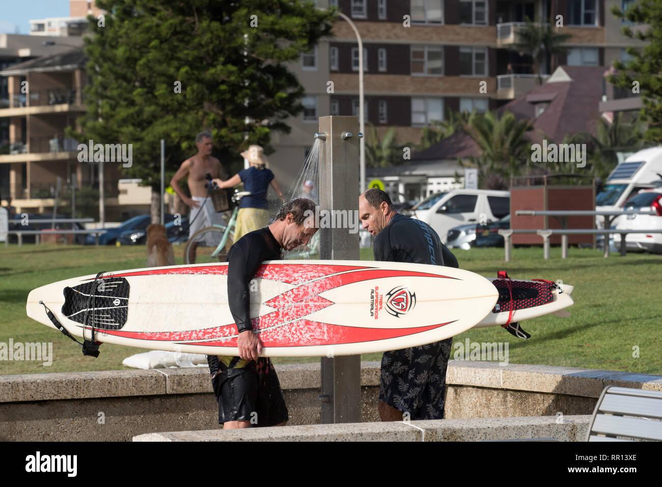 Les hommes âgés moyens de se laver et de leurs planches de surf sous une douche extérieure à North Steyne réserver sur Sydney Manly Beach en Australie Photo Stock