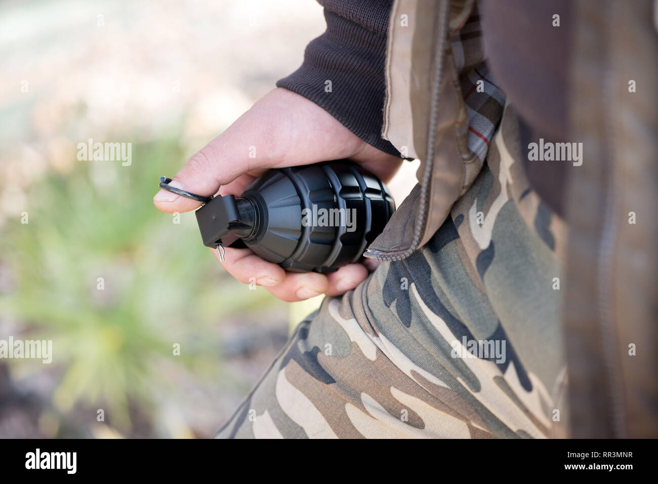 Close up portrait of a man in camouflage tenant une grenade dans sa main Photo Stock